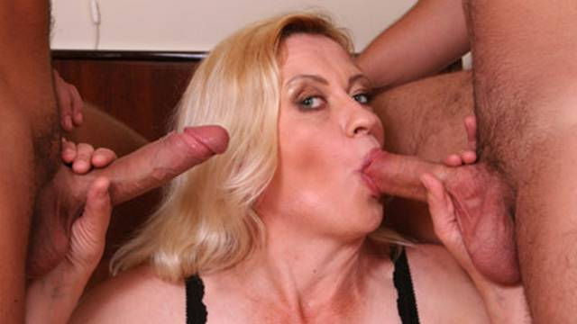 Mature beauty kisses two cocks